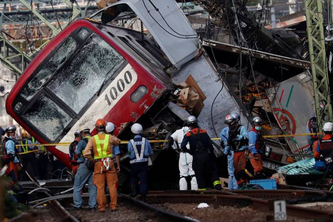 Rescue officers, police and railway company employees work at the scene where a train derailed during a collision with a truck in Yokohama, near Tokyo