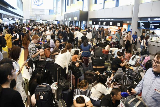 Passengers are stranded after railways and subway operators suspended their services due to Typhoon Faxai, at Narita airport in Narita