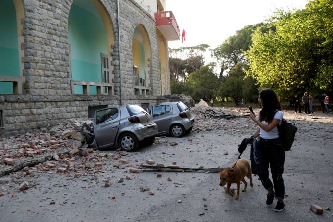 A woman with a dog walks past destroyed cars and a damaged building after an earthquake in Tirana