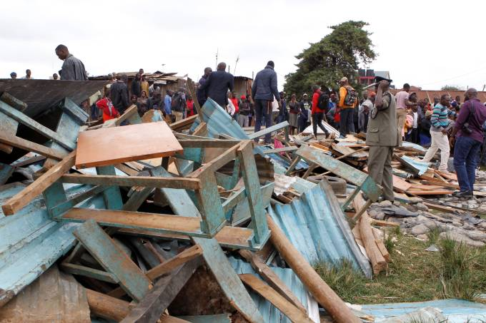 A police officer stands near the debris of a collapsed school classroom, in Nairobi