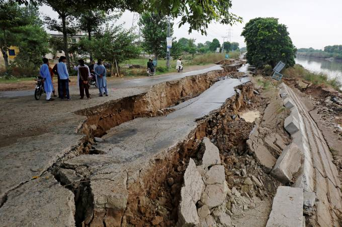 People gather near a damaged road after an earthquake in Mirpur