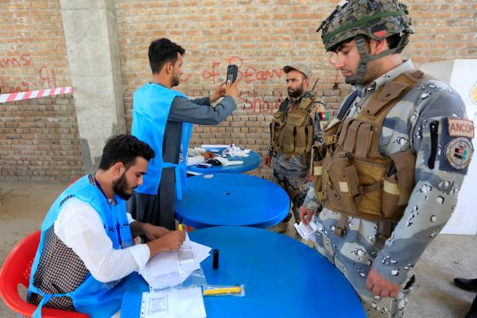 Afghan policemen arrive to cast their votes in presidential election in Jalalabad, Afghanistan