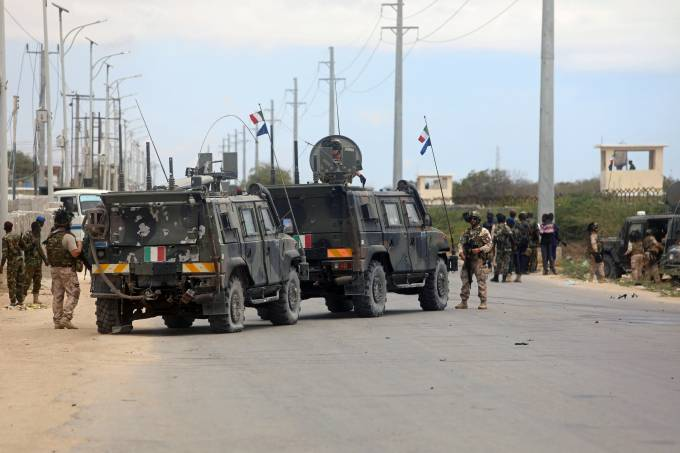 Italian and Somali security forces are seen near damaged armoured vehicles at the scene of an attack on an Italian military convoy in Mogadishu