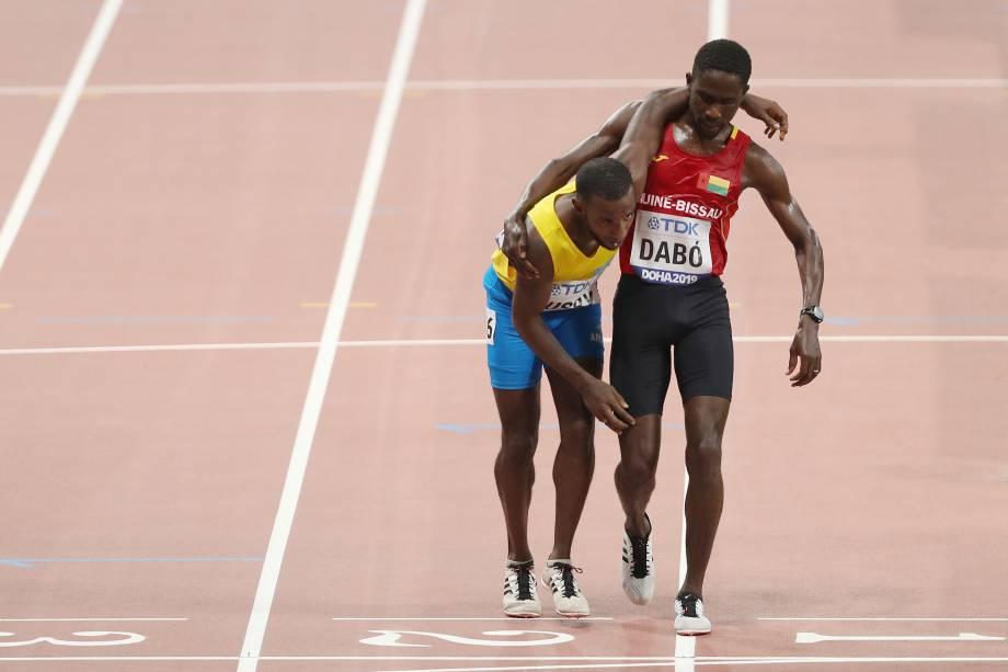Braima Suncar Dabo, da Guiné-Bissau, ajuda Jonathan Busby de Aruba na linha de chegada nas mangas de 5000 metros masculinos, em Doha, no Catar