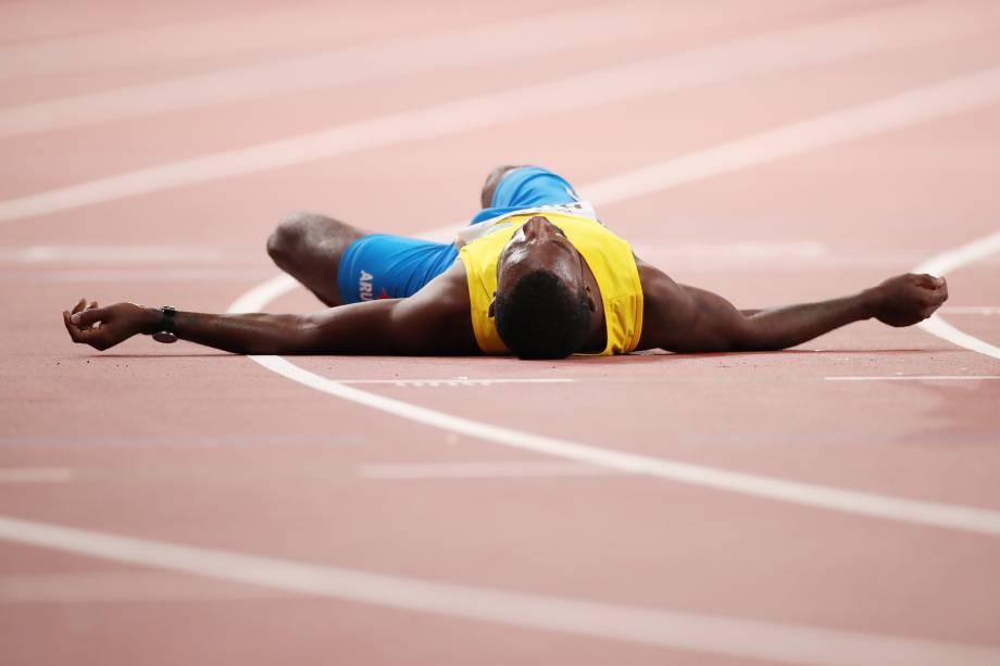 Jonathan Busby, de Aruba, encontra-se na pista depois de ser ajudado na linha de chegada nas mangas de 5000 metros masculinos, em Doha, no Catar