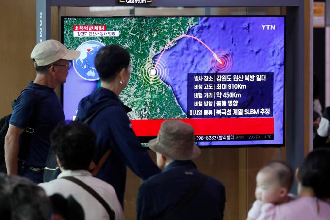 People watch a TV broadcasting a news report on North Korea firing a missile that is believed to be launched from a submarine, in Seoul