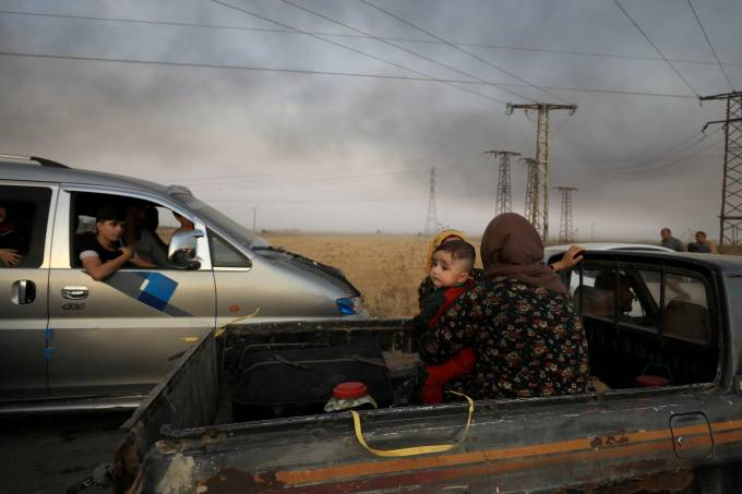 FILE PHOTO: A woman with a baby sits at a back of a truck as they flee Ras al Ain town