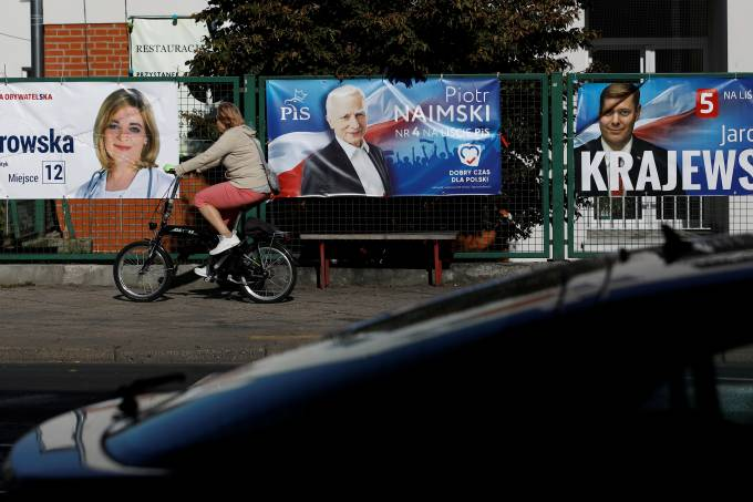 A woman rides her bicycle in front of election banners in Warsaw