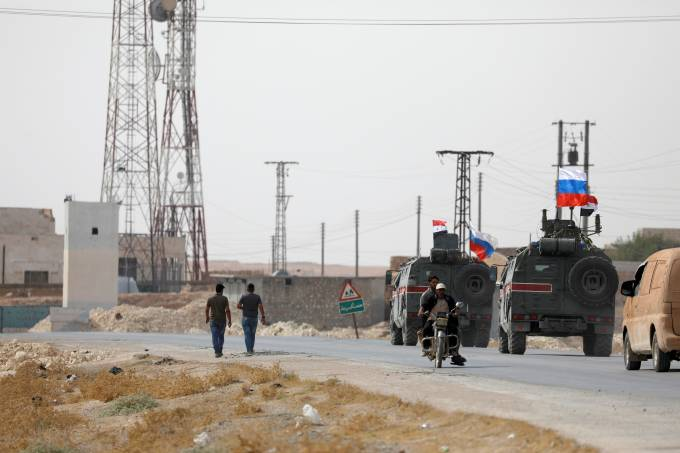 Russian and Syrian national flags flutter on military vehicles near Manbij