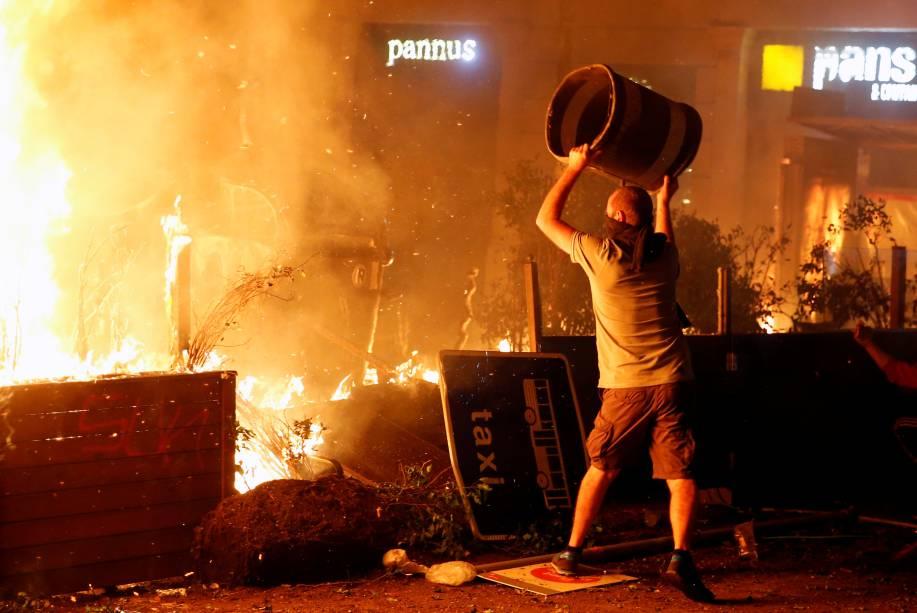 Durante os protestos da greve geral, um manifestante catalão usa mais uma lata de lixo para alimentar o fogo - 18/10/2019