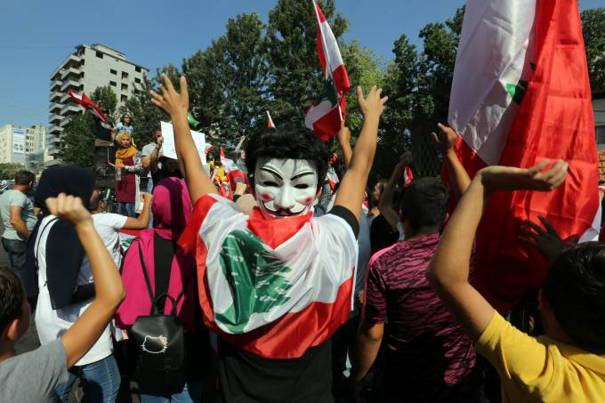 Demonstrator wearing a mask takes part in an anti-government protest in the southern city of Nabatiyeh