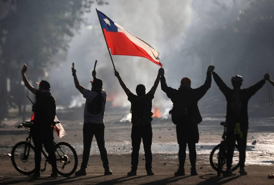 Chilenos seguram a bandeira nacional durante protestos em Santiago: repressão ao velho estilo - 21/10/2019