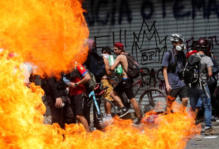 Manifestantes passam por barricada de fogo em Santiago: não à política econômica - 23/10/2019