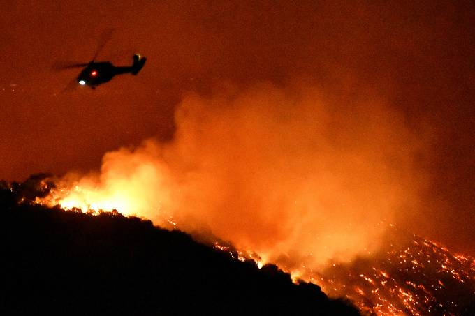 A firefighting helicopter flies over the Getty Fire as it burns in the hills west of the 405 freeway in the hills of West Los Angeles, California