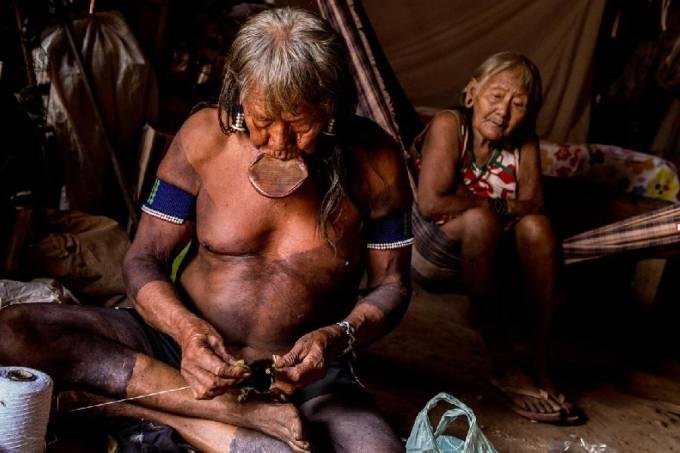 Cacique Raoni faz artesanato em sua aldeia ao lado da mulher, Bekwyijkà