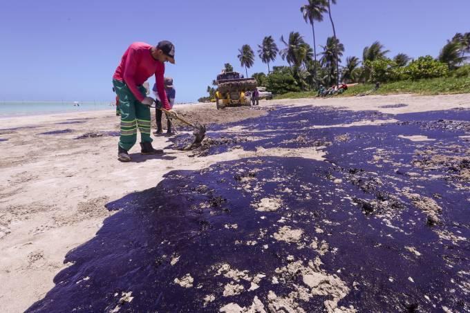 Funcionários limpam manchas de óleo poluem a praia Ponta do Mangue, em Maragogi (AL)