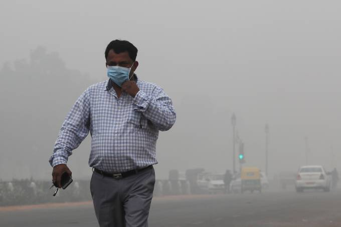 A man wearing a mask walks on a smoggy morning in New Delhi