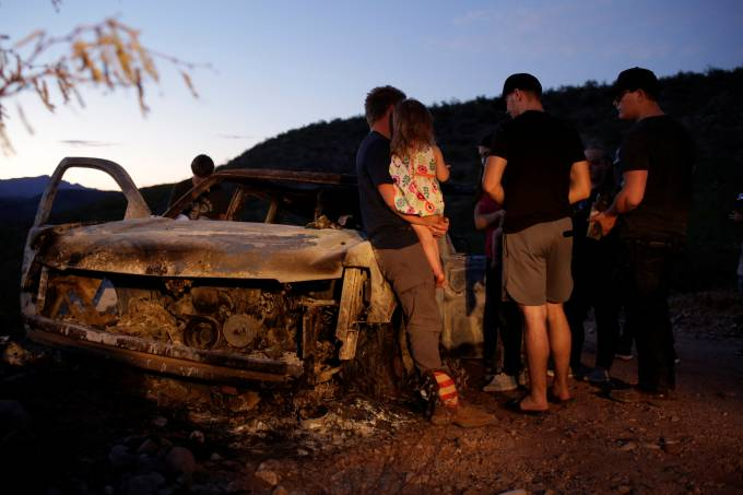 Relatives of slain members of Mexican-American families belonging to Mormon communities observe the burnt wreckage of a vehicle where some of their relatives died, in Bavispe