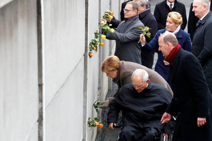 A chanceler alemã Angela Merkel, o presidente do Parlamento Wolfgang Schaeuble e o diretor da Fundação do Muro de Berlim Axel Klausmeier colocam flores no memorial durante cerimônia de 30 anos da queda do Muro