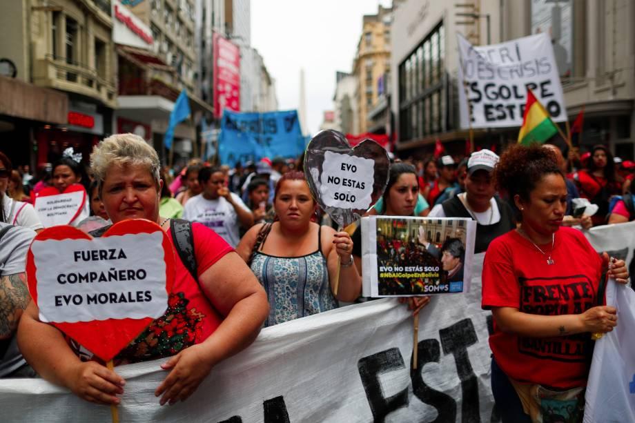 """Pessoas segurando cartazes lendo """"Força companheiro Evo Morales"""" e """"Você não está sozinho"""" participam de uma manifestação em apoio ao presidente boliviano Evo Morales depois que ele anunciou sua renúncia no domingo, em Buenos Aires, Argentina."""