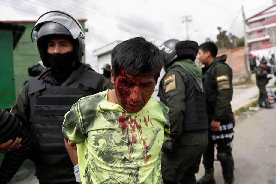 Um policial detém um homem ferido durante os confrontos entre partidários do presidente boliviano Evo Morales, e partidários da oposição, em La Paz.