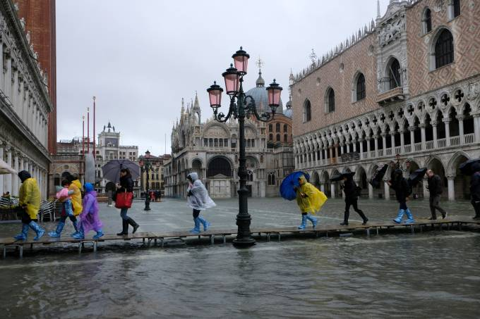 People walk on a catwalk in the flooded St.Mark's Square during a period of seasonal high water