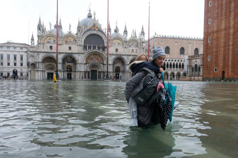 Uma mulher carregando uma crianças nos braços na Preça de São Marcos, que está inundada, em Veneza - 12/11/2019