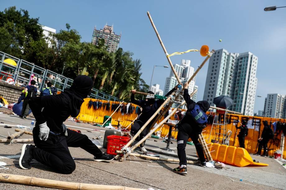 Manifestantes estudantis usam um estilingue gigante improvisado para arremessar bolas de tênis através de uma barricada como lazer na Universidade Batista de Hong Kong, China