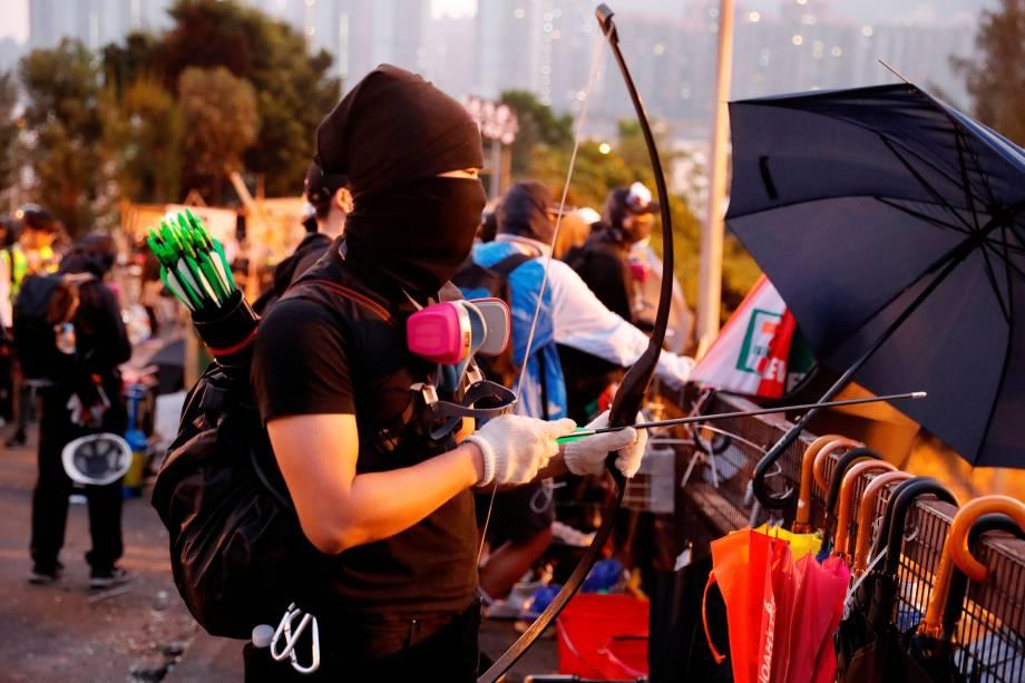 Um manifestante antigoverno utiliza um arco e flecha improvisado durante um impasse com a polícia de choque na Universidade Chinesa de Hong Kong, em Hong Kong, na China