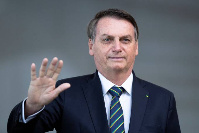 Brazil's President Jair Bolsonaro greets the media prior to a meeting of leaders of the BRICS emerging economies at the Itamaraty palace in Brasilia