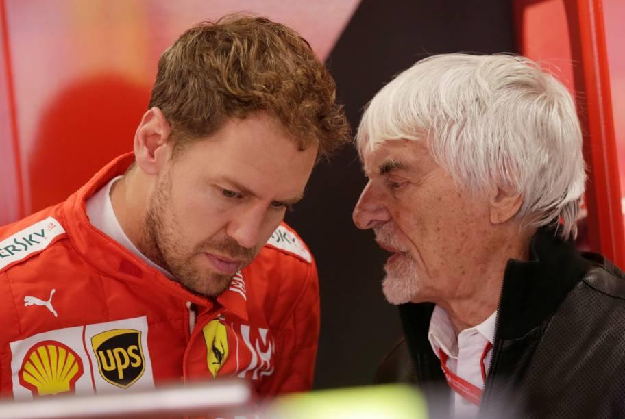 Sebastian Vettel da Ferrari e ex-presidente da F1 Bernard Ecclestone em boxes antes do treino
