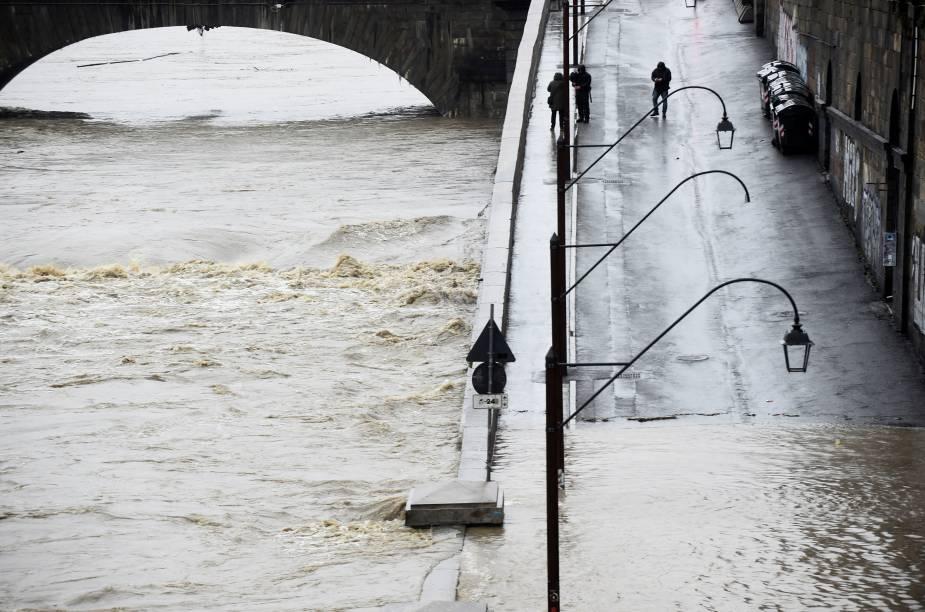 Pessoas caminham próximo às margens do rio Pó, quando ele atinge um nível crítico, enquanto chuvas torrenciais varrem a Itália inundando partes do centro da cidade de Turim, na Itália — 24/11/2019