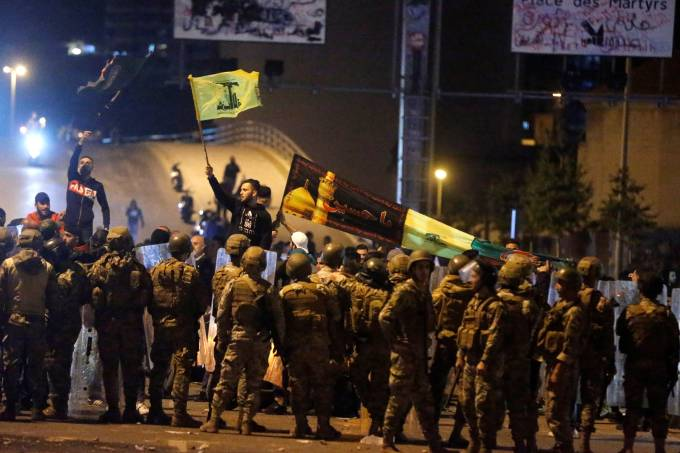 Supporters of the Lebanese Shi'ite groups Hezbollah and Amal carry flags as Lebanese army soldiers are deployed in Beirut