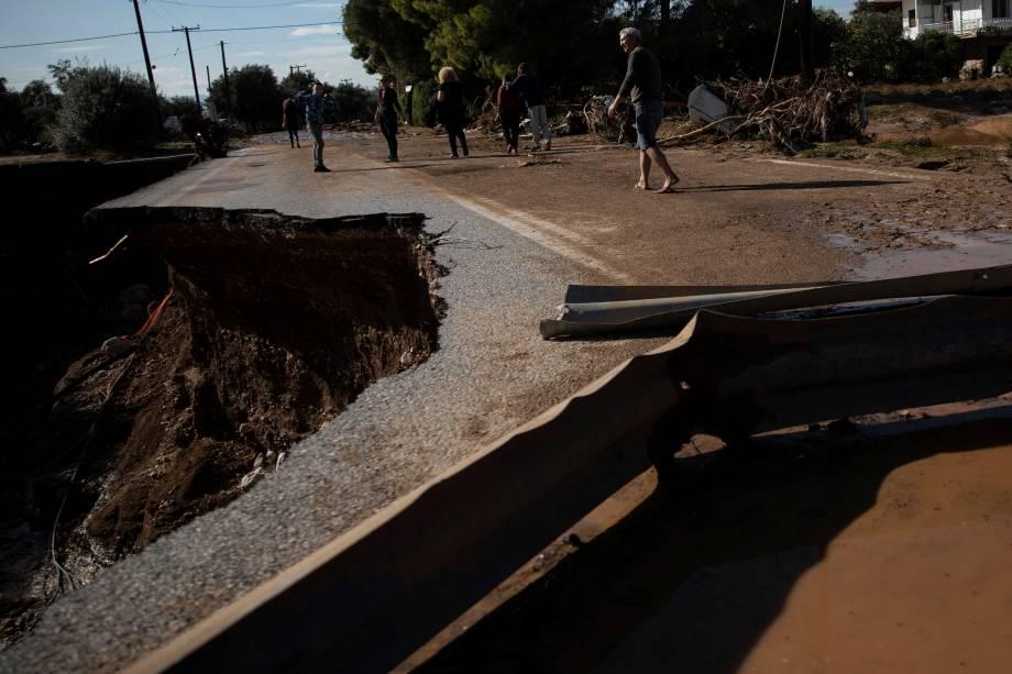 Habitantes atravessam ponte parcialmente desmoronada após inundações na cidade de Kineta, Grécia - 25/11/2019