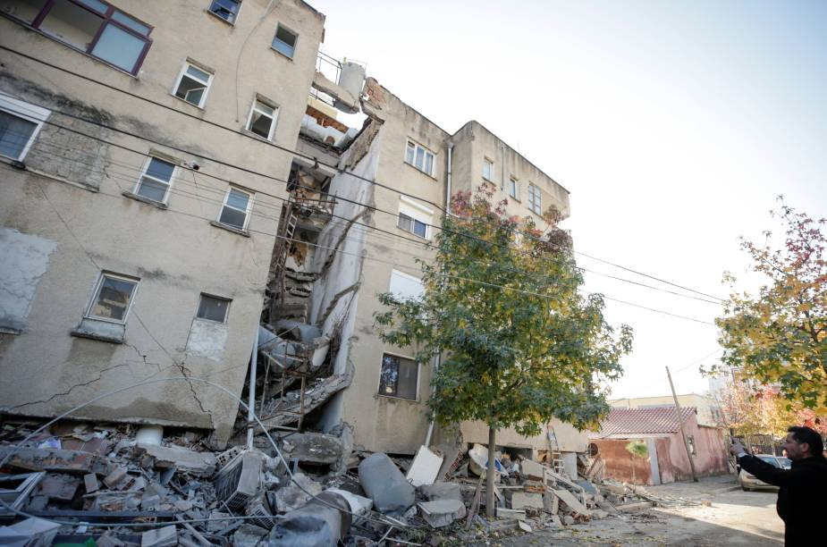 Um homem tira fotos de um prédio danificado em Durres, Albânia, após o terremoto — 26/11/2019