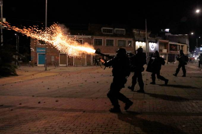 Riot police fire tear gas as demonstrators protest at the National University as a national strike continues in Bogota