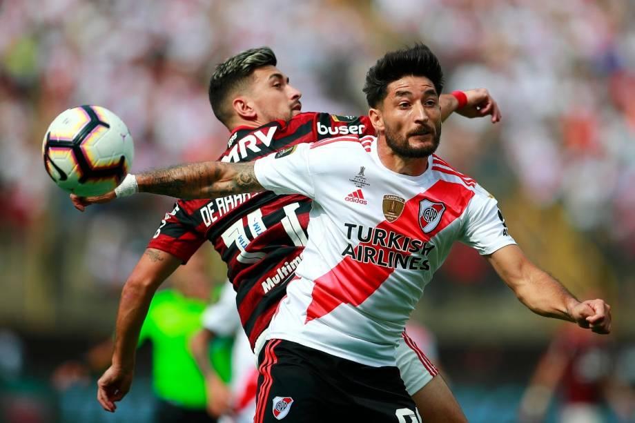 O argentino Milton Casco disputa bola com o uruguaio De Arrascaeta, do Flamengo, na final da Copa Libertadores