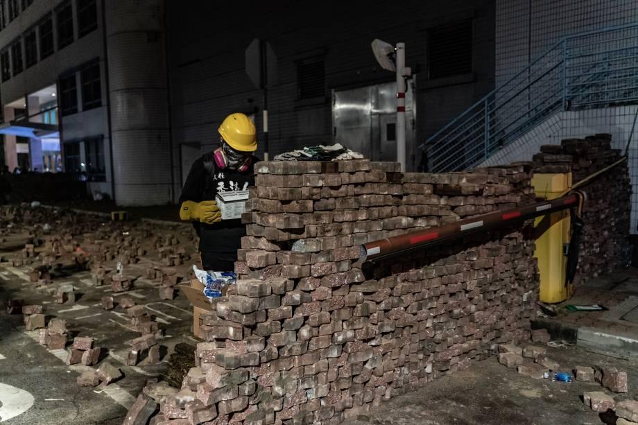 Um manifestante pró-democracia constrói uma parede de tijolos durante uma manifestação na Universidade Chinesa de Hong Kong