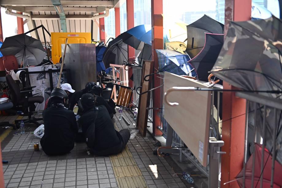 Manifestantes são vistos sentados em uma passarela barricada dentro da Universidade Politécnica no distrito de Tsim Sha Tusi durante um protesto antigovernamental em Hong Kong, China