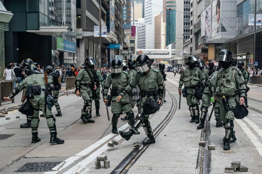 A polícia de choque limpa tijolos em uma rua onde manifestantes tentaram bloquear o tráfego no Distrito Central em Hong Kong, China