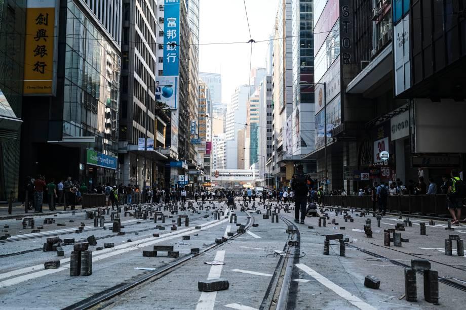 Manifestantes montam tijolos para bloquear o tráfego durante um protesto no distrito central de Hong Kong.