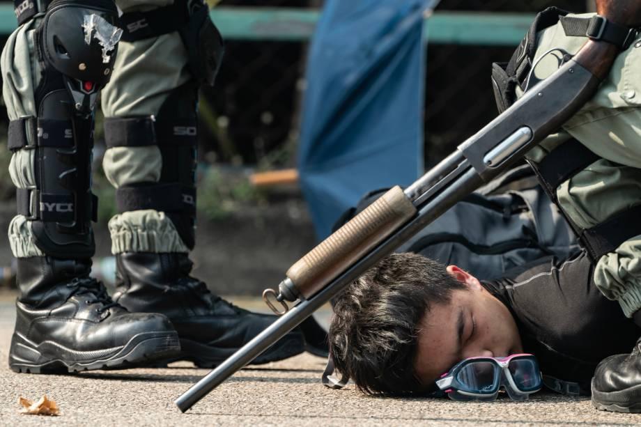 Um manifestante é detido pela polícia enquanto tenta escapar da Universidade Politécnica de Hong Kong