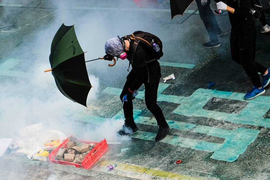 Um manifestante coloca água em uma lata de gás lacrimogêneo durante a manifestação em Hong Kong