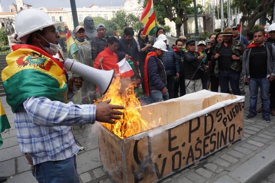 Manifestantes anti-Morales queimam uma caixa simulando um caixão com o nome de Evo Morales na antiga casa do governo Palacio Quemado, neste domingo em La Paz, Bolívia. Minutos depois, Morales anunciou sua renúncia em Chimore, Cochabamba, após três semanas de protestos por sua tentativa de reeleição depois que o exército e a polícia retiraram seu apoio.