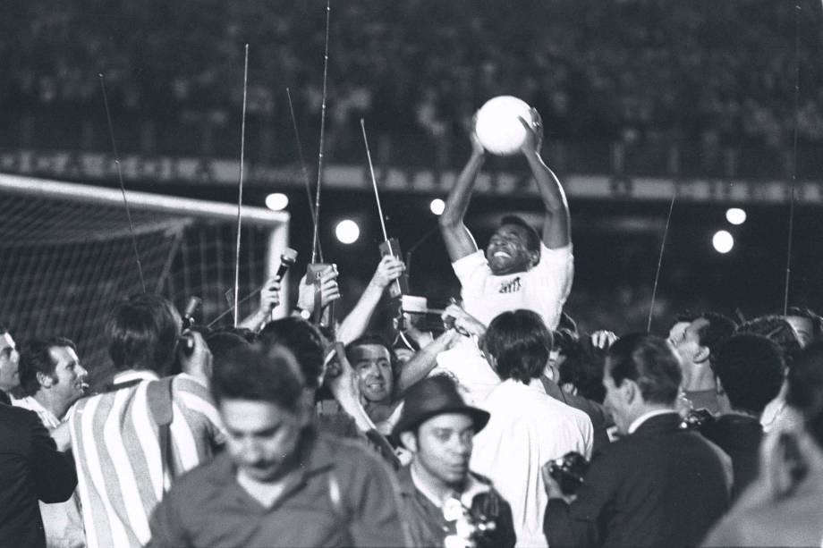 Carregado nos braços, a partida foi paralizada para Pelé comemorar em campo seu feito memorável