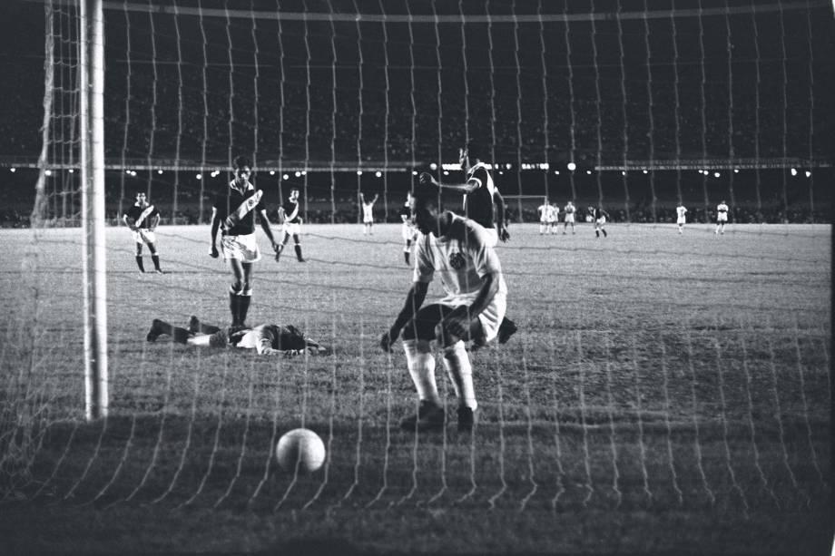 Pelé busca a bola no fundo das redes após converter o pênalti de gol de número 1.000