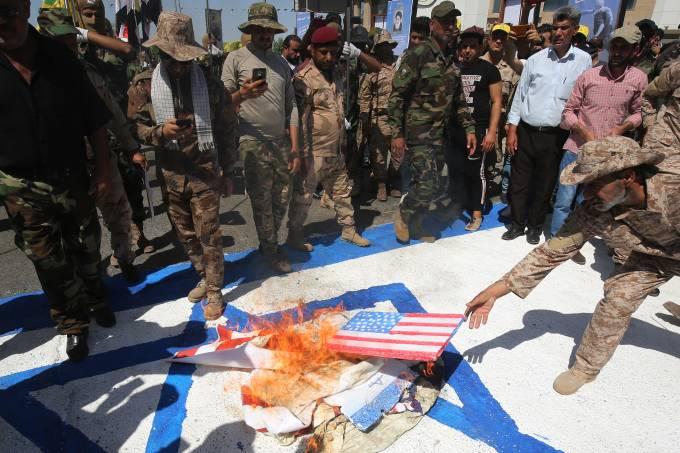 Facções iraquianas queimam bandeiras dos Estados Unidos e de Israel durante um desfile militar em Bagdá, em 31 de maio de 2019