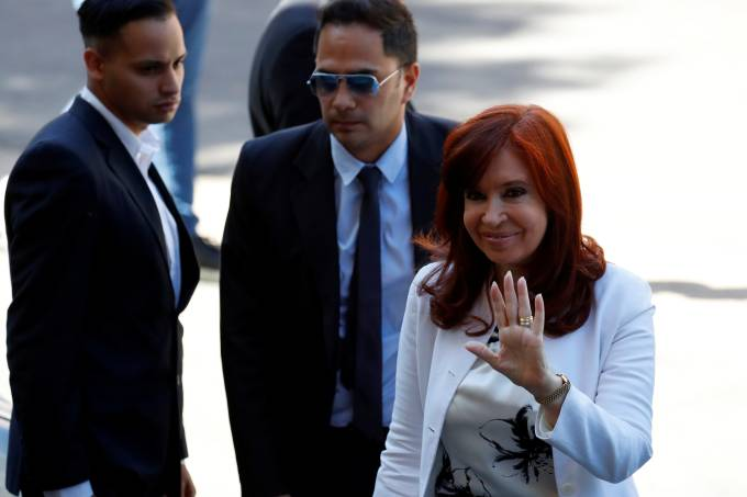 Argentina's former President and Vice President-elect Cristina Fernandez de Kirchner waves as she arrives to a hearing of a corruption trial on a case involving her, in Buenos Aires