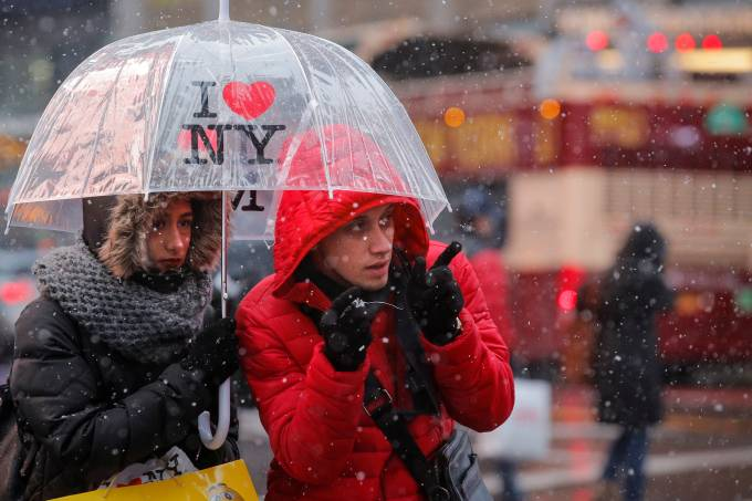 Tourists walk through the snow in Times Square in New York