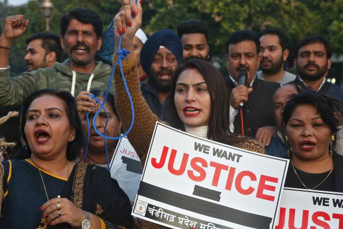 People shout slogans during a protest against the alleged rape and murder of a 27-year-old woman, in Chandigarh